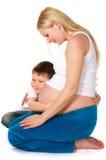 Cabrito que abraza a su madre embarazada Fotografía de archivo