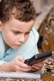 Cabrito que juega al juego electrónico Imagen de archivo libre de regalías