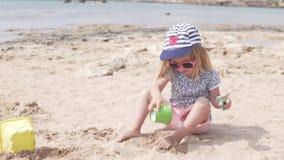 Cabrito que juega con la arena Juegos de la niña en la playa metrajes