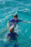 Cabrito que juega en agua Imagen de archivo libre de regalías