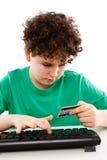 Cabrito usando compras de la tarjeta de crédito en línea Foto de archivo