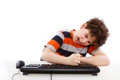 Cabrito usando el ordenador en el fondo blanco Foto de archivo libre de regalías