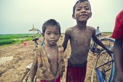 Cabritos camboyanos pobres que juegan con la bicicleta Imagenes de archivo