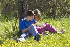 Cabritos con los teléfonos móviles Fotos de archivo
