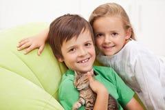 Cabritos con su nuevo animal doméstico imagen de archivo