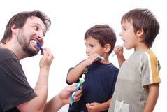 Cabritos de enseñanza del hombre joven cómo limpiar los dientes fotos de archivo libres de regalías
