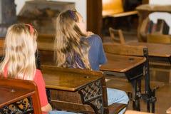 Cabritos de la escuela en escritorios. Imagen de archivo