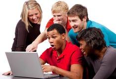 Cabritos de la universidad que miran una pantalla de ordenador Imágenes de archivo libres de regalías