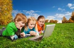 Cabritos emocionados con la computadora portátil en parque Imágenes de archivo libres de regalías