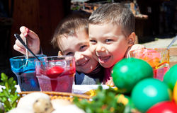 Cabritos emocionados que colorean los huevos de Pascua Fotos de archivo libres de regalías