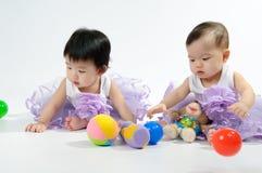 Cabritos en la alineada púrpura que juega el juguete Imagen de archivo