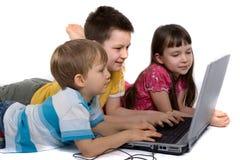 Cabritos en suelo con el ordenador portátil Fotos de archivo