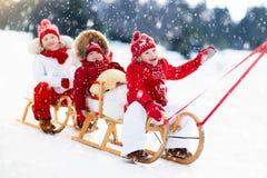 Cabritos en trineo Trineo de los niños Diversión de la nieve del invierno Imagen de archivo