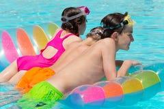 Cabritos en un flotador de la piscina imagen de archivo
