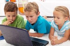 Cabritos enfocados que miran el ordenador portátil Fotografía de archivo
