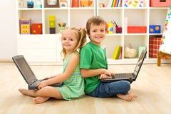 Cabritos felices con las computadoras portátiles que se sientan en el suelo Fotografía de archivo libre de regalías