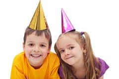 Cabritos felices con los sombreros del partido Foto de archivo libre de regalías