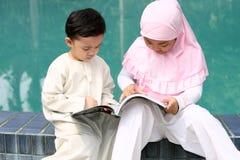Cabritos musulmanes que leen un libro Imagen de archivo libre de regalías