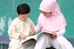 Cabritos musulmanes que leen un libro imagenes de archivo