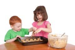 Cabritos que cuentan las galletas de viruta de chocolate para cocer al horno Fotografía de archivo libre de regalías