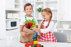 Cabritos que desempaquetan las tiendas de comestibles Foto de archivo libre de regalías