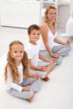 Cabritos que hacen la relajación de la yoga con su madre Foto de archivo libre de regalías