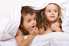 Cabritos que juegan bajo el edredón en cama Fotografía de archivo libre de regalías