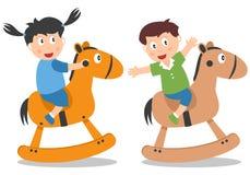 Cabritos que juegan con el caballo de oscilación Foto de archivo