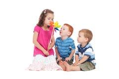 Cabritos que juegan con el molino de viento del juguete Fotografía de archivo