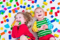 Cabritos que juegan con los bloques coloridos Fotografía de archivo
