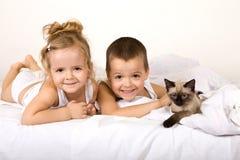 Cabritos que juegan con su gatito en la cama Imágenes de archivo libres de regalías