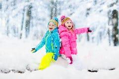 Cabritos que juegan en nieve Juego de niños al aire libre en nevadas del invierno imagen de archivo libre de regalías