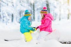 Cabritos que juegan en nieve Juego de niños al aire libre en nevadas del invierno fotos de archivo libres de regalías