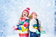 Cabritos que juegan en nieve Juego de niños al aire libre en nevadas del invierno foto de archivo