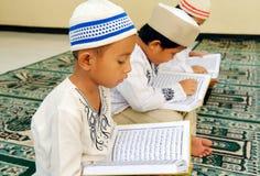 Cabritos que leen Koran foto de archivo