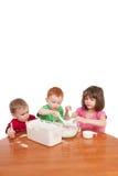 Cabritos que miden y que mezclan la harina en tazón de fuente de la cocina Imagen de archivo