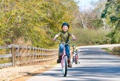 Cabritos que montan las bicis Imagen de archivo libre de regalías