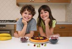 Cabritos que preparan la torta con sabor a fruta Fotos de archivo libres de regalías