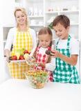 Cabritos que preparan una ensalada fresca sana Imagen de archivo