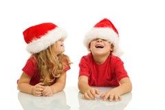 Cabritos que se divierten con los sombreros de la Navidad Fotos de archivo