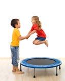 Cabritos que se divierten con un trampolín en la gimnasia Foto de archivo libre de regalías