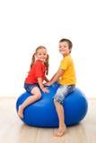 Cabritos que se divierten el jugar con una bola grande fotografía de archivo libre de regalías
