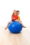 Cabritos que tienen la diversión y ejercicios con una bola grande Foto de archivo
