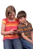 Cabritos texting Imagenes de archivo