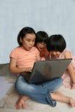 Cabritos usando la computadora portátil foto de archivo libre de regalías