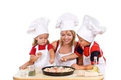 Cabritos y su madre que preparan una pizza Imágenes de archivo libres de regalías