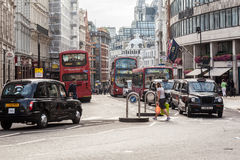 Cabs and Red Buses London. The busy St Paul Courtyard street with black taxis and red buses in downtown London, England Royalty Free Stock Image