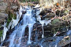 Cacading water. An cascading water fall with ice on the side at an state park in massachusetts Stock Photography