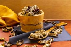 Cacahuete con la c?scara y la c?scara en un cuenco al lado de cubiertos y de un mantel de madera fotografía de archivo libre de regalías