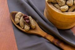Cacahuete con la c?scara y la c?scara en un cuenco al lado de cubiertos y de un mantel de madera fotografía de archivo